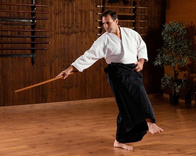 Mannelijke vechtsportinstructeur met houten stok in de oefenruimte