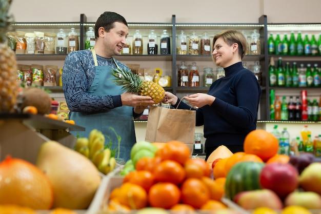 Mannelijke verkoper geeft een ambachtelijke tas met boodschappen aan een vrouwelijke klant