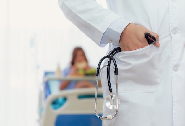 Mannelijke verloskundige arts professionals houdt stethoscoop en zwangere vrouw onscherpe achtergrond.
