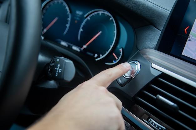Mannelijke vinger drukt op de start-stop-motorknop op het dashboard van het autodashboard en de snelheidsmeter van de auto;