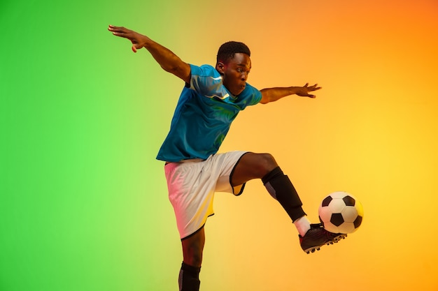 Mannelijke voetbal, voetballer training in actie geïsoleerd op verloop studio in neonlicht