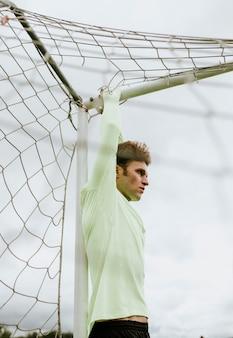 Mannelijke voetbalkeeper die zich op een dwarsbalk uitrekt