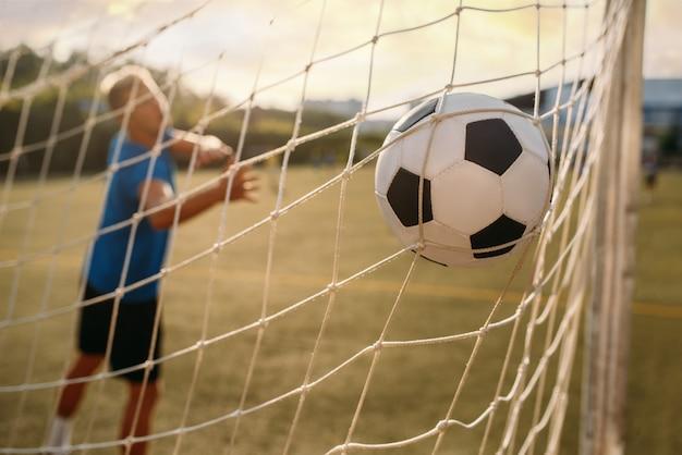 Mannelijke voetbalkeeper miste de bal en kreeg een doelpunt. voetballer op buitenstadion, training voor wedstrijd, voetbaltraining