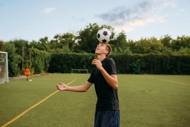 Mannelijke voetballer propt de bal met zijn hoofd op het veld. voetballers op openluchtstadion, teamtraining voor wedstrijd