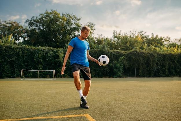 Mannelijke voetballer stopt de bal met zijn voet op het veld. voetballer op openluchtstadion, training voor voetbalwedstrijd