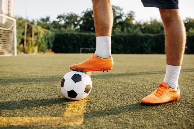 Mannelijke voetballerbenen met bal die zich online op het gebied bevinden. voetballer op openluchtstadion, training voor voetbalwedstrijd