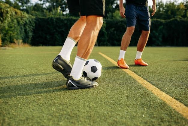 Mannelijke voetballers spelen met bal online op het veld. voetballer op openluchtstadion, training voor voetbalwedstrijd