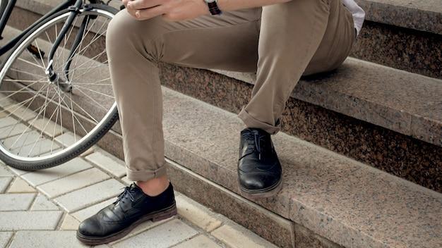 Mannelijke voeten en vintage fiets op stenen trappen op straat in de stad.