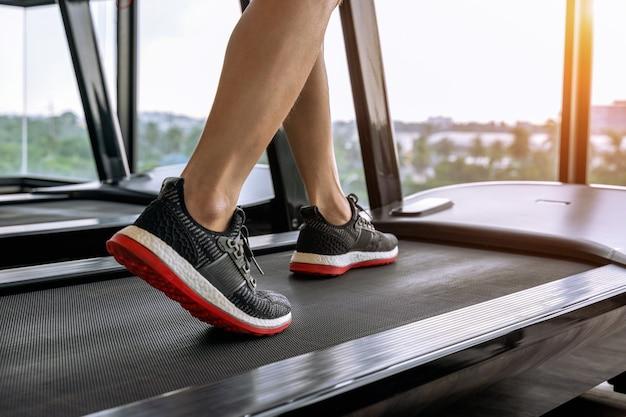 Mannelijke voeten in sneakers uitgevoerd op de loopband in de sportschool. oefening concept.