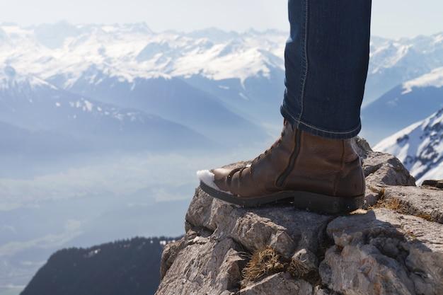 Mannelijke voeten op de rand van een houten bankje.