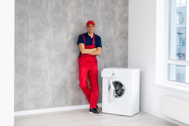 Mannelijke volwassen reparateur wasmachine in de badkamer controleren