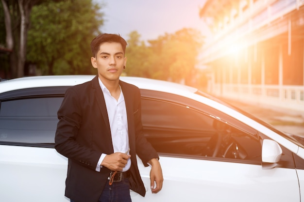 Mannelijke volwassen zakenman in een pak en een auto sleutel in zijn hand te houden. witte auto's op de achtergrond