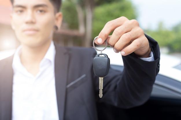 Mannelijke volwassen zakenman in een pak en een auto sleutel in zijn hand te houden