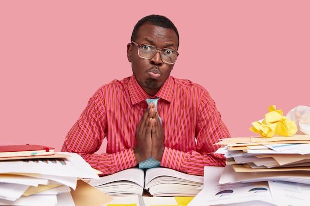 Mannelijke volwassene met zwarte huid, heeft medelijden met gezichtsuitdrukkingen, smeekt hem nog een kans te geven om de situatie te verbeteren en zich beter voor te bereiden op het seminar