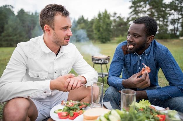 Mannelijke vrienden buiten eten barbecue
