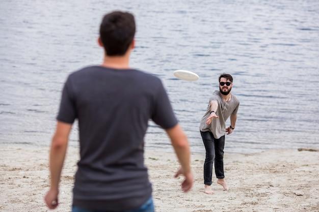 Mannelijke vrienden die frisbee op strand dichtbij water spelen