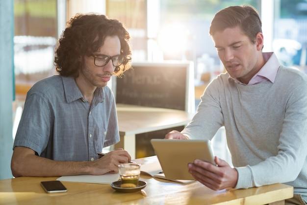 Mannelijke vrienden die op digitale tablet bespreken
