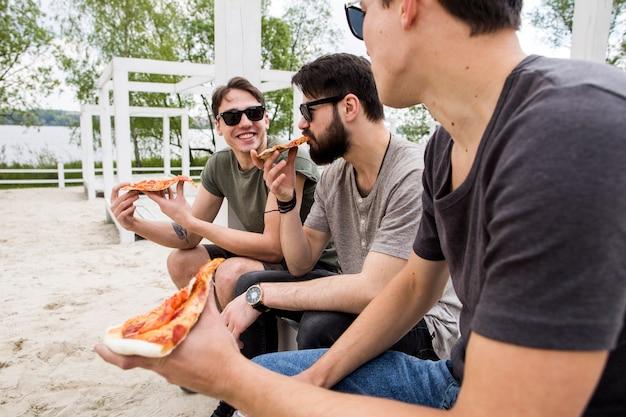 Mannelijke vrienden die van pizza op strand genieten