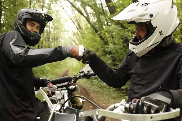 Mannelijke vrienden in helmen maken vuist hobbel terwijl ze elkaar steunen, ze genieten van motorrijden in het bos