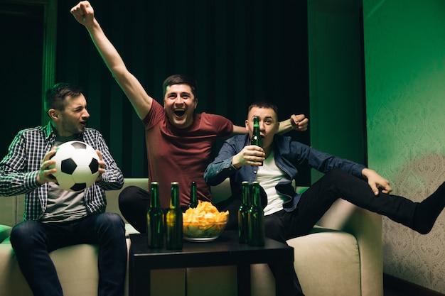 Mannelijke vrienden kijken naar sportkanaal verzamelden drie knappe gelukkige blanke vriendelijke mannen