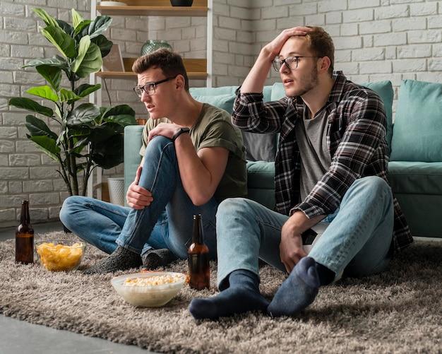 Mannelijke vrienden kijken samen naar sport op tv terwijl ze snacks en bier hebben