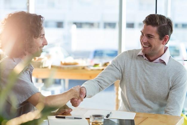 Mannelijke vrienden schudden handen in café