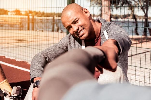 Mannelijke vriendschap. aardige afro-amerikaanse man kijkt naar zijn vriend zittend op de grond