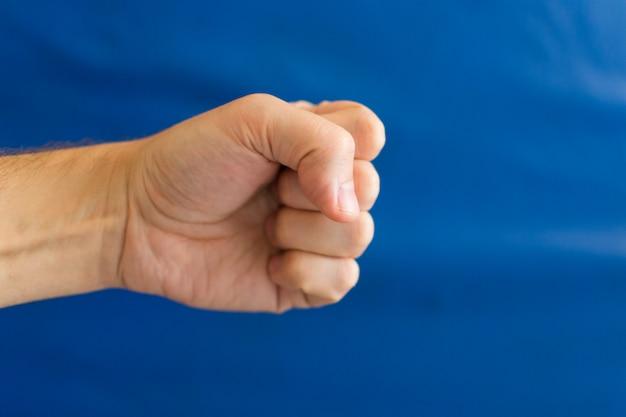 Mannelijke vuist op een blauwe muur in de sportschool