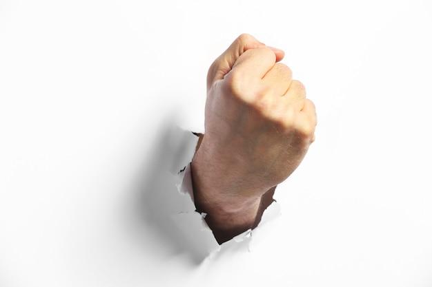 Mannelijke vuist ponsen door papier, op wit