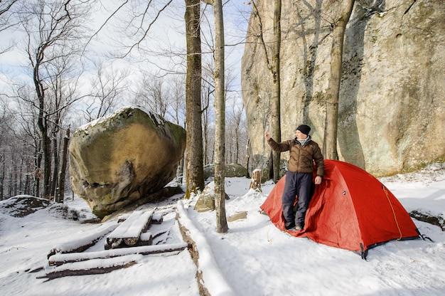 Mannelijke wandelaar bijna zijn rode tent in de bergen