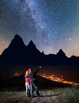 Mannelijke wandelaar knuffelen roodharige meisje en shows op sterren