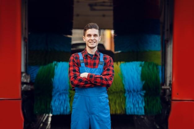 Mannelijke wasmachine in uniform op automatische autowasstraat met kleurrijke borstel