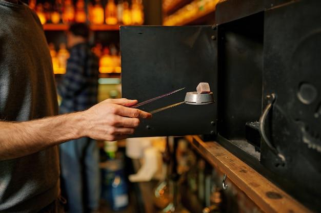 Mannelijke waterpijpmaker, kolenvoorbereiding in de bar