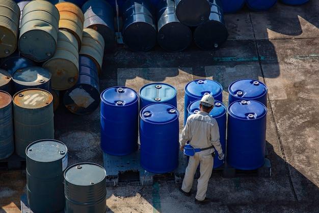 Mannelijke werkinspectie olievaten groen of chemische vaten horizontaal gestapeld