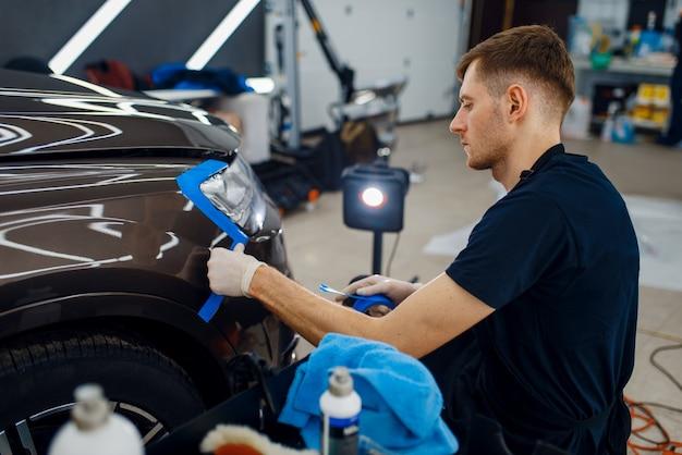 Mannelijke werknemer bereidt auto-oppervlak voor op het aanbrengen van beschermfolie