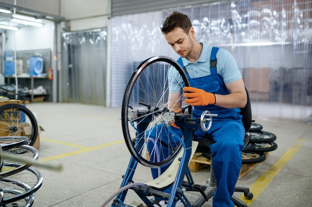 Mannelijke werknemer bij de werktuigmachine controleert de fietsrand op de fabriek. montage fietswielen in werkplaats