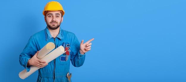 Mannelijke werknemer blauwdrukken houden en opzij wijzen met wijsvinger, ongeschoren ingenieur gele helm en blauw uniform dragen