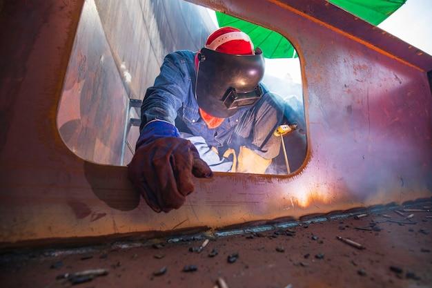 Mannelijke werknemer die beschermende kleding draagt en reparatie ponton mangat lassen rook industriële constructie olie vlotter opslagtank in besloten ruimtes.