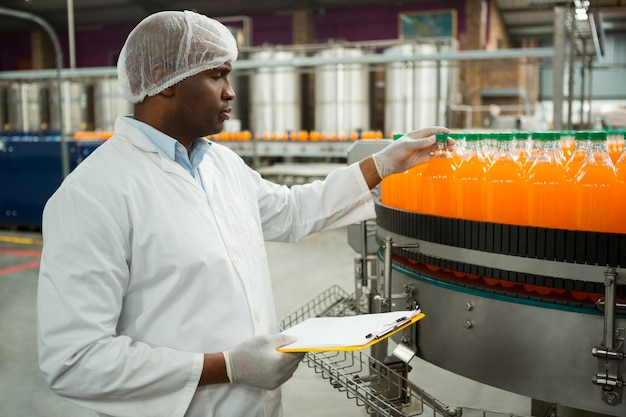 Mannelijke werknemer die flessen in sap-fabriek onderzoekt