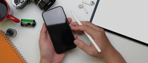 Mannelijke werknemer die smartphone boven wit bureau met tablet, camera en andere levering gebruiken