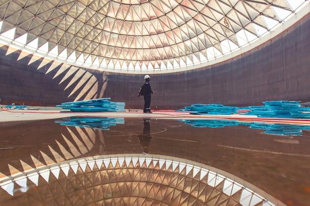 Mannelijke werknemer dossier opnemen visuele inspectie tank in de besloten ruimte is de verlichting dakkoepel