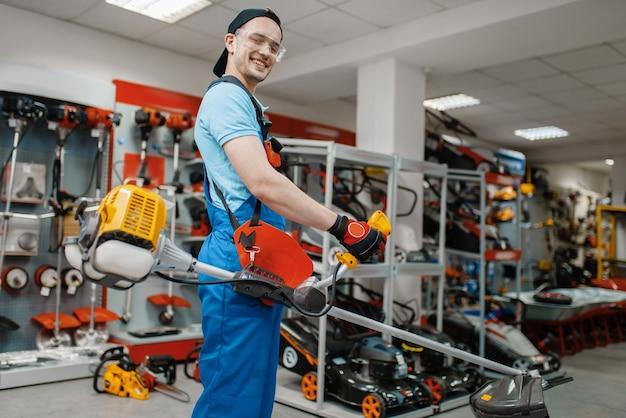 Mannelijke werknemer houdt gas trimmer in gereedschapsopslag. keuze uit professionele apparatuur in ijzerhandel, supermarkt voor elektrische instrumenten