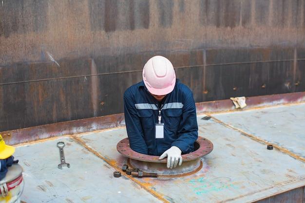 Mannelijke werknemer in de visuele inspectietank van de pontontank in de besloten ruimte is de ventilatorlucht;