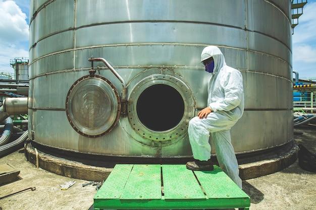 Mannelijke werknemer in mangat brandstoftank olie chemische beschermende kleding gebied besloten ruimte gevaarlijk