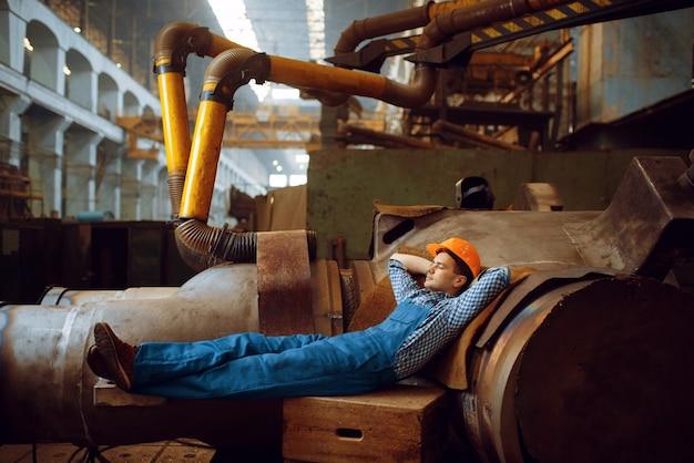 Mannelijke werknemer in uniform en helm rusten tijdens de lunch op fabriek. metaalverwerkende industrie, industriële fabricage van staalproducten