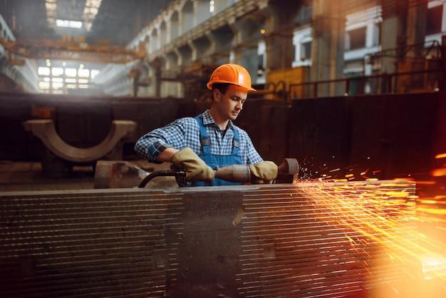Mannelijke werknemer in uniform en helm werkt met metalen werkstukken op fabriek. metaalverwerkende industrie, industriële fabricage van staalproducten