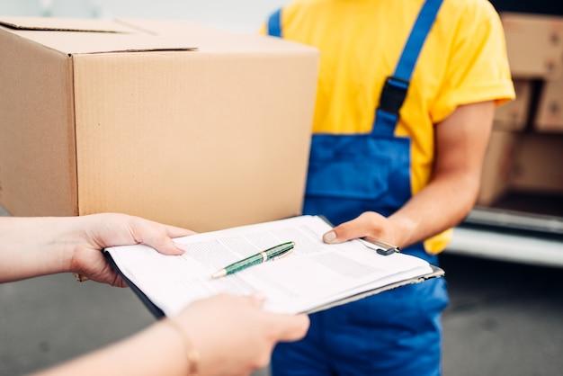 Mannelijke werknemer in uniform geeft pakket aan de klant