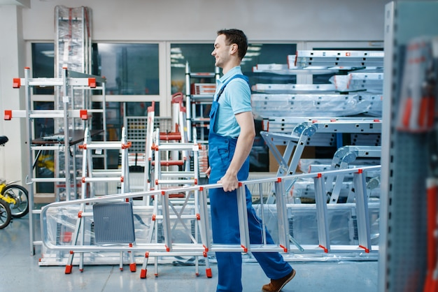 Mannelijke werknemer in uniform houdt nieuwe aluminium trapladders in gereedschapsopslag. afdeling met ladders, materiaalkeuze in ijzerhandel, instrumentensupermarkt