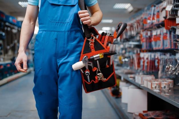 Mannelijke werknemer in uniform houdt toolbox in gereedschapsopslag. keuze uit professionele apparatuur in ijzerhandel, instrumentensupermarkt