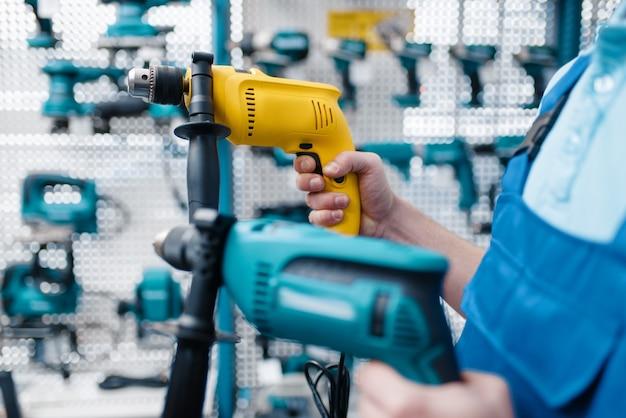 Mannelijke werknemer in uniform houdt twee elektrische boormachines vast in gereedschapswinkel